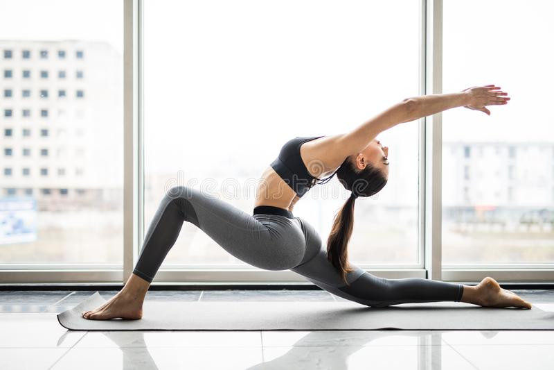 De jonge mooie vrouw het praktizeren mening van yogavensters op de achtergrond Het concept van de vrijheid De kalmte en ontspant, stock foto