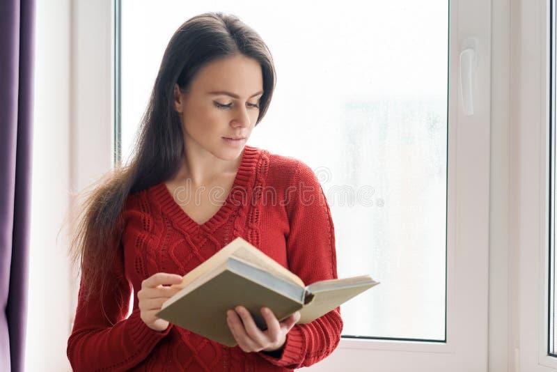 De jonge mooie vrouw in het rode boek van de sweaterlezing, meisje bevindt zich dichtbij venster in wolkenkrabber op bewolkte dag royalty-vrije stock fotografie