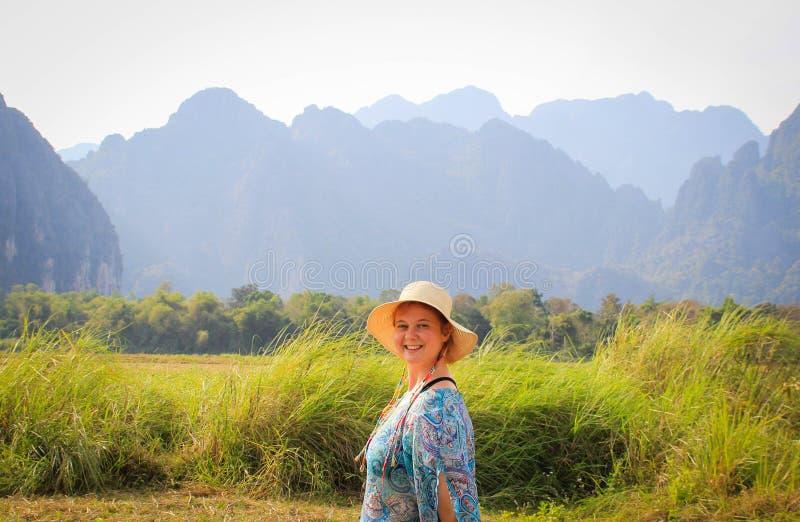 De jonge mooie vrouw in hoed en blauwe kleding glimlacht bij zonsopgang tegen de achtergrond van mooie karst bergen in het dorp stock afbeeldingen