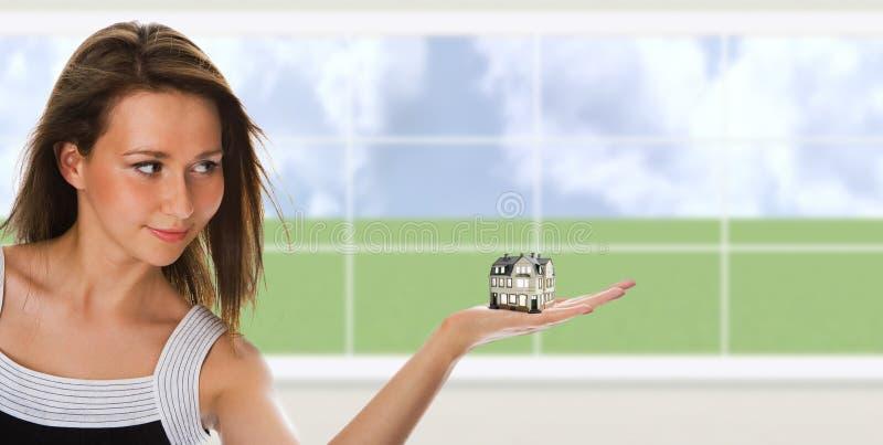De jonge mooie vrouw houdt een klein huis op hand stock foto