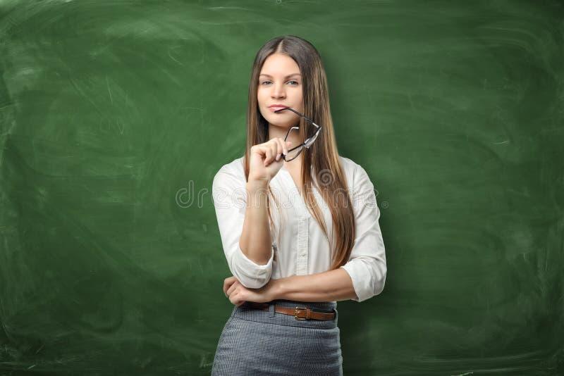 De jonge mooie vrouw houdt haar glazen en glimlacht op groene bordachtergrond stock afbeeldingen