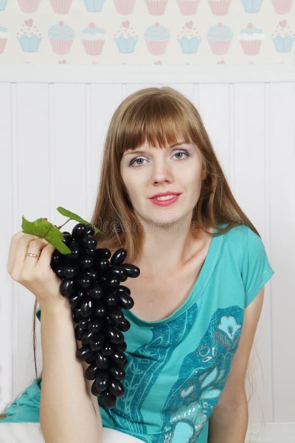 De jonge mooie vrouw houdt zwarte druif royalty-vrije stock afbeelding