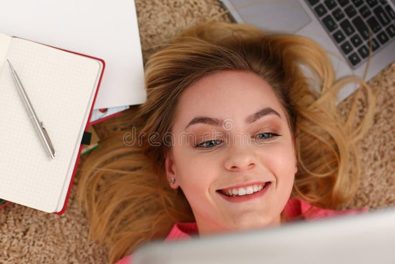De jonge mooie vrouw ligt op vloer heeft heel wat tablet van de het werkgreep in wapens royalty-vrije stock foto