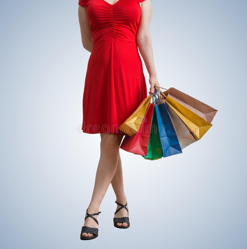 De jonge mooie vrouw loopt en houdt het winkelen zakken in handen stock afbeeldingen