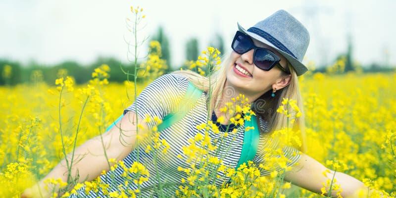De jonge mooie vrouw loopt langs een bloeiend gebied op een zonnige dag royalty-vrije stock foto