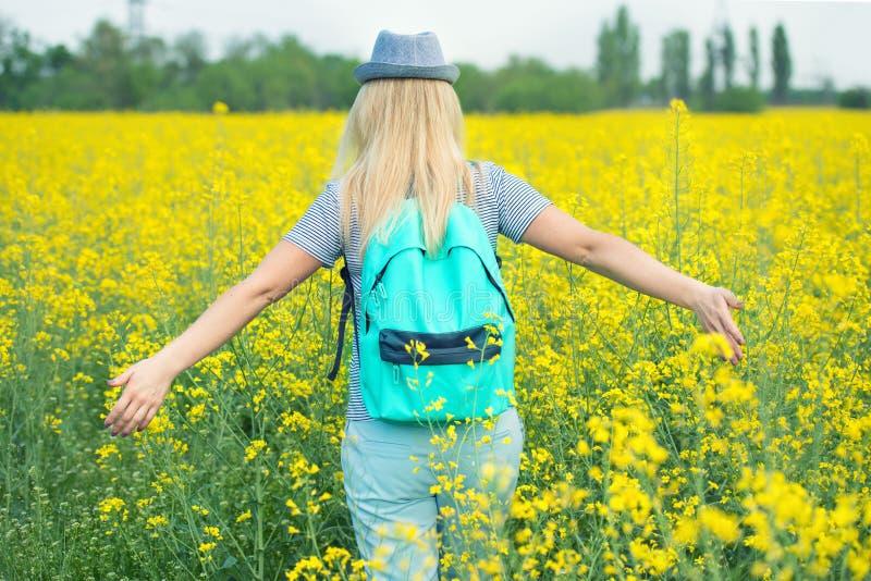 De jonge mooie vrouw loopt langs een bloeiend gebied op een zonnige dag royalty-vrije stock afbeelding