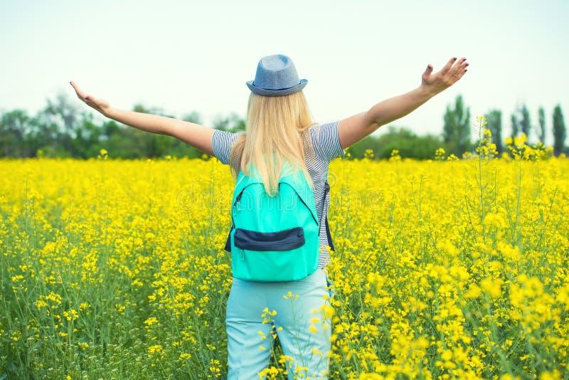 De jonge mooie vrouw loopt langs een bloeiend gebied op een zonnige dag royalty-vrije stock foto's