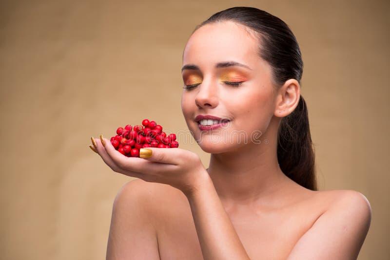 De jonge mooie vrouw met bessen in schoonheidsconcept stock fotografie