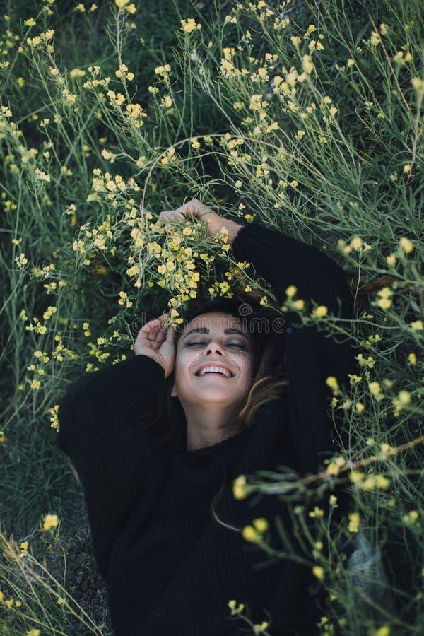De jonge mooie vrouw met het heldere glanzen maakt omhoog op een groene weide stock afbeelding