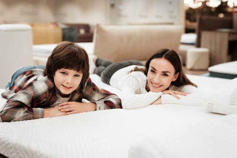 De jonge mooie vrouw met leuk weinig jongen ligt op bed in matrasopslag royalty-vrije stock afbeeldingen
