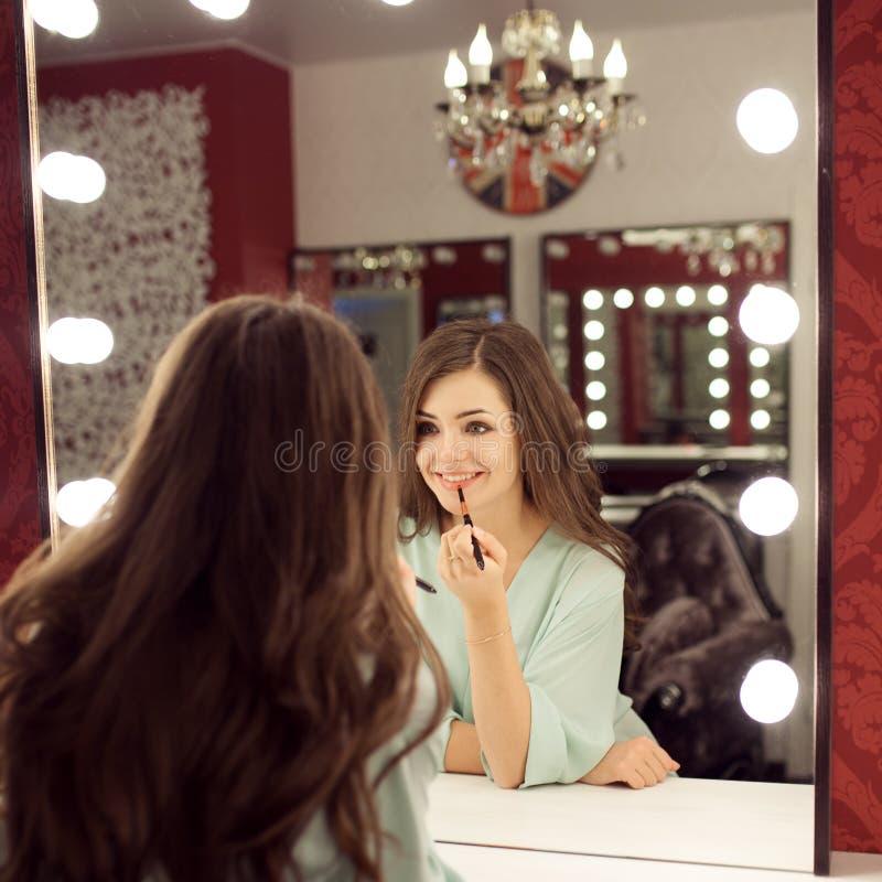 De jonge mooie vrouw met maakt omhoog en bezinning in kleedkamer stock foto's
