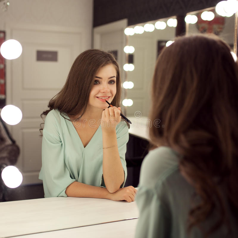 De jonge mooie vrouw met maakt omhoog en bezinning in kleedkamer stock fotografie