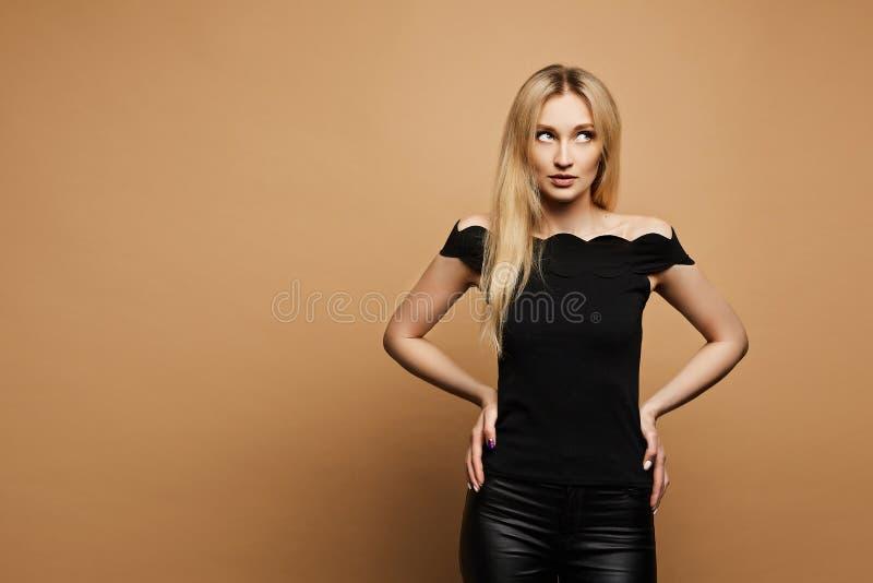 De jonge mooie vrouw met slank perfect lichaam en met blondehaar in zwart leer hijgt en in een zwarte blouse bij stock afbeeldingen
