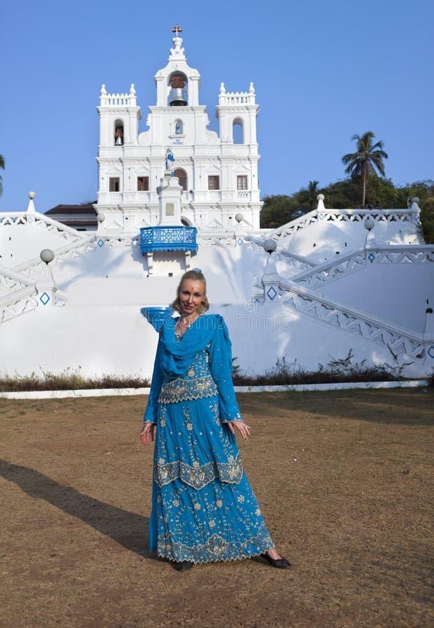 De jonge mooie vrouw in nationale Indische kleren dichtbij de Katholieke tempel, Goa stock afbeeldingen