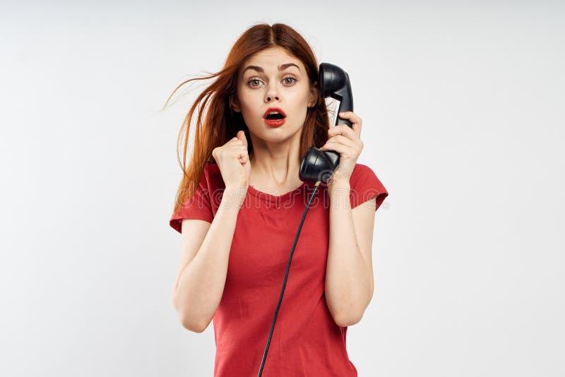 De jonge mooie vrouw op witte achtergrond in rode kleding houdt landline telefoon, emoties stock foto