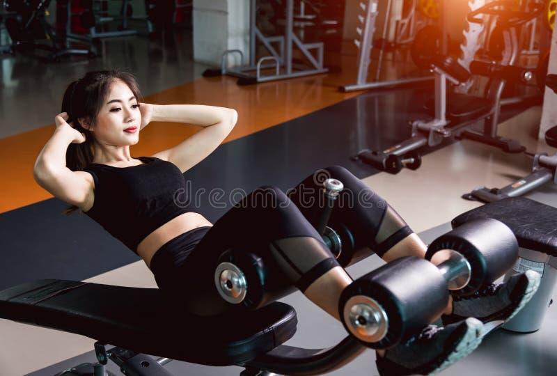 De jonge mooie vrouw opleiding die abs van de materiaalmachine gebruiken zit omhoog training royalty-vrije stock fotografie