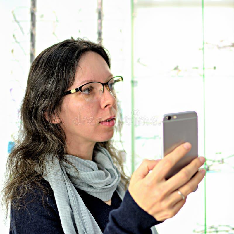 De jonge mooie vrouw probeert oogglazen bij een eyewear winkel met hulp van een winkelmedewerker en aandelen in sociale media geb royalty-vrije stock foto