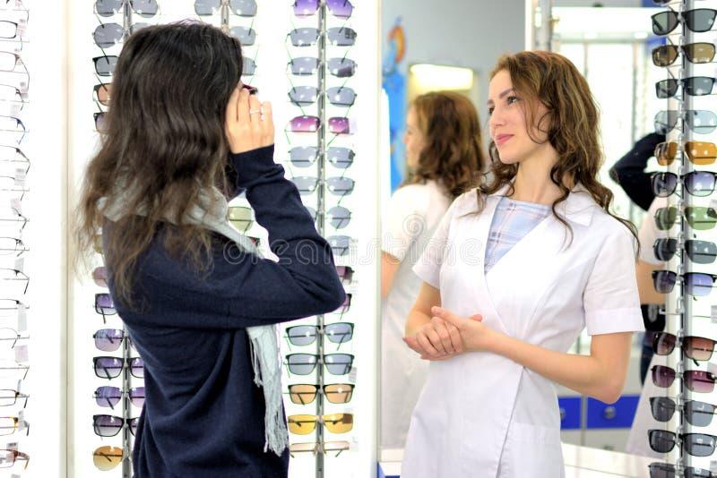 De jonge mooie vrouw probeert zonglazen bij een eyewear winkel met hulp van een winkelmedewerker royalty-vrije stock afbeelding