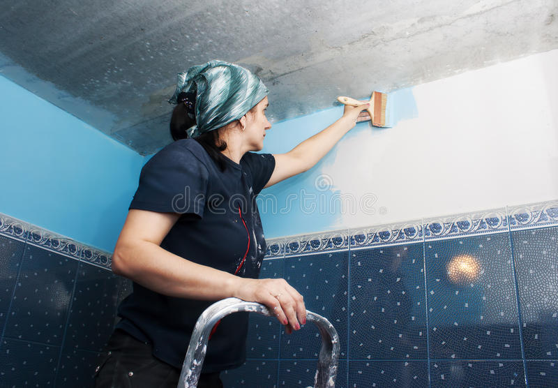 De jonge mooie vrouw schildert de muur royalty-vrije stock fotografie
