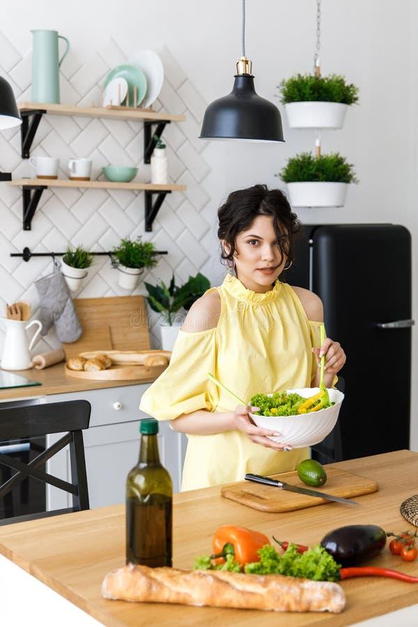 De jonge mooie vrouw snijdt een avocado op een houten saladeraad cooking Voorbereiding van verse groentesalade royalty-vrije stock foto's