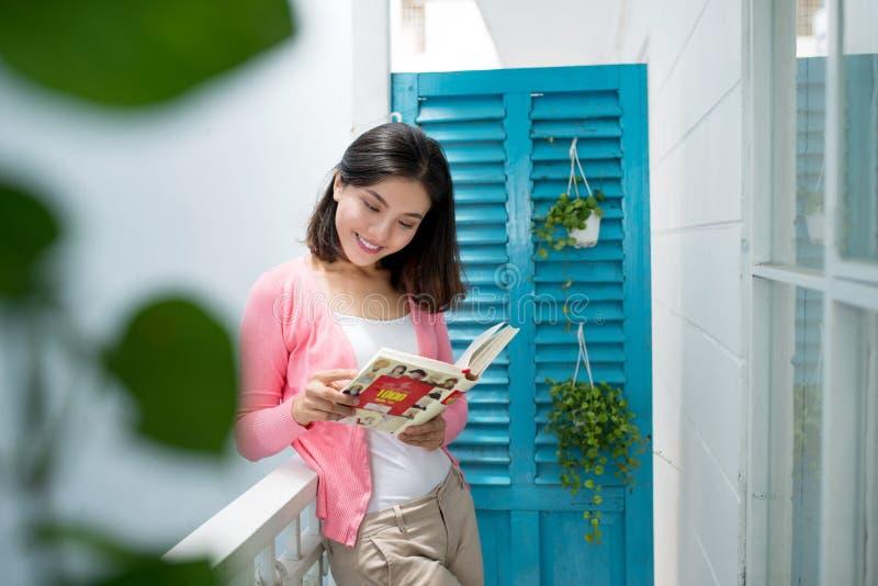 De jonge mooie vrouw status dichtbij venster die een boek lezen geniet van van royalty-vrije stock afbeelding