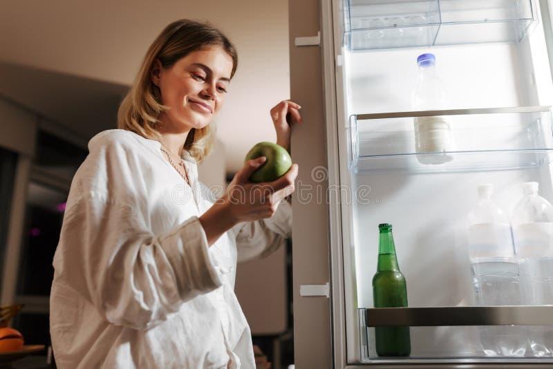 De jonge mooie vrouw status op keuken bij nacht opende dichtbij koelkast gelukkig kijkend op groene appel stock foto's