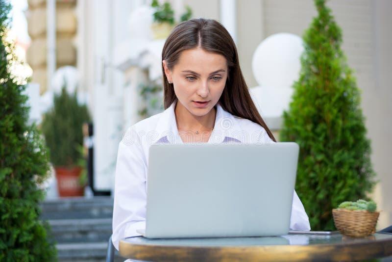 De jonge mooie vrouw zit met binnen laptop en een smartphone royalty-vrije stock foto