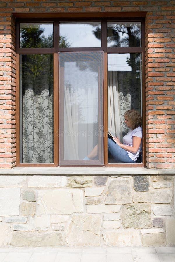 De jonge mooie vrouw zit op de vensterbank en leest een boek royalty-vrije stock afbeelding