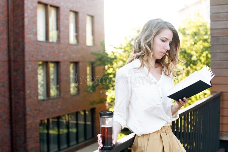De jonge mooie vrouwenzitting bij geopende venster het drinken thee en het lezen van een boek geniet van van rust stock foto's