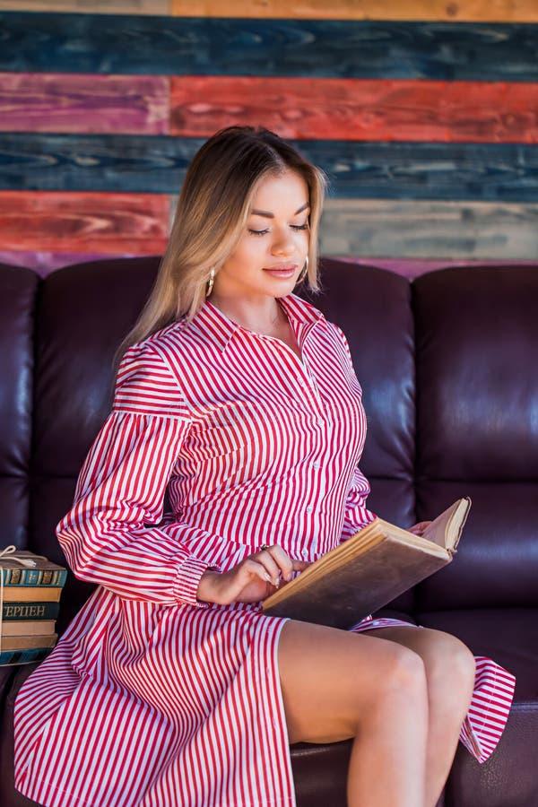 De jonge mooie vrouwenzitting en de lezing een boek genieten van van rust stock foto's