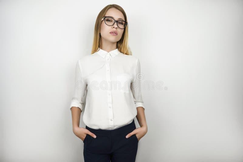 De jonge mooie zelfverzekerde bedrijfsvrouw in oogglazen na succesvolle commerciële vergadering isoleerde witte achtergrond royalty-vrije stock afbeelding