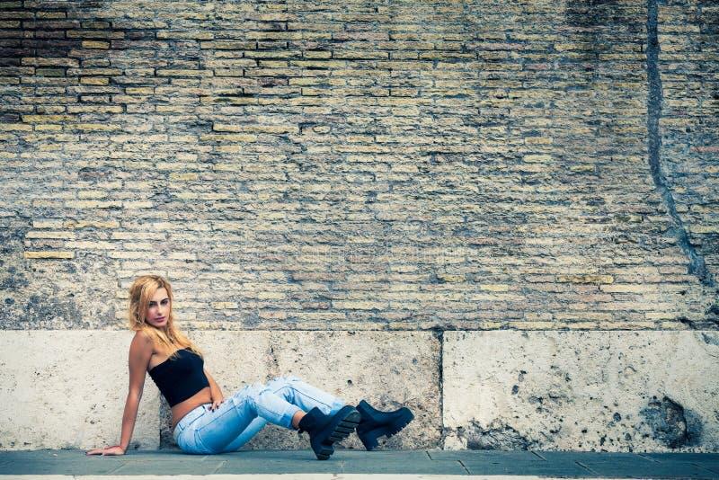 De jonge mooie zitting van het blondemeisje, oude bakstenen muur De jeugdmanier stock fotografie