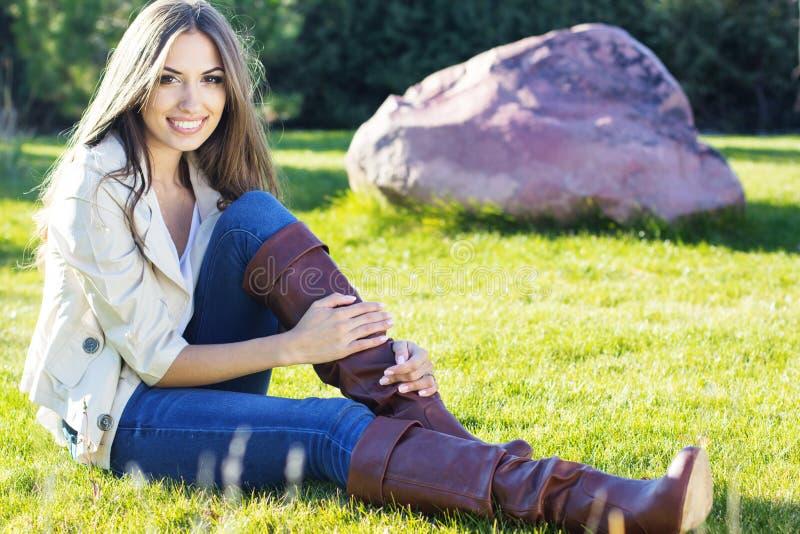 De jonge mooie zitting van het tienermeisje op groen gras stock fotografie