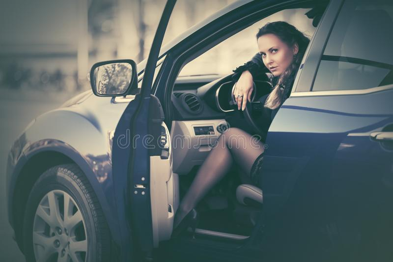 De jonge mooie zitting van de maniervrouw in een auto stock foto
