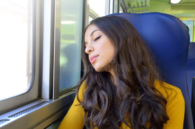 De jonge mooie zitting van de vrouwenslaap in de trein De reizende zitting van de treinpassagier in een zetel en slaap stock afbeelding