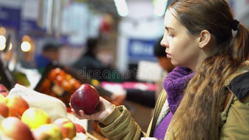 De jonge, mooie zwangere vrouw in de supermarkt selecteert verse organische appelen