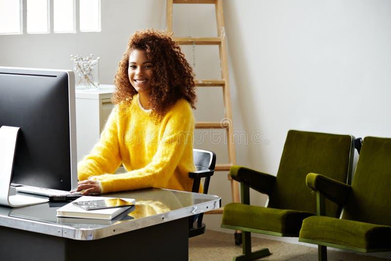 De jonge mooie zwarte meisjeswerken in huisbureau stock foto's