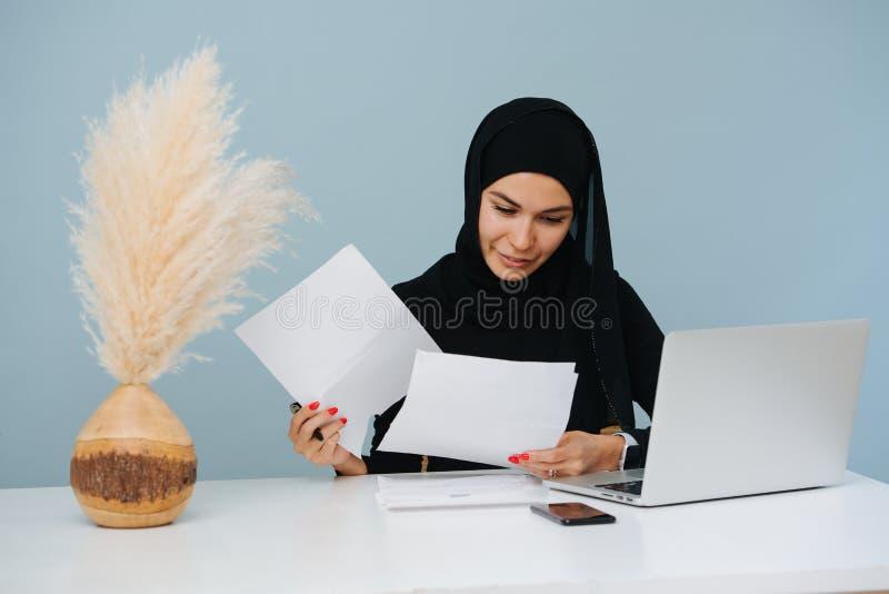 De jonge moslimdocumenten van de vrouwenholding, die door documenten kijken royalty-vrije stock afbeelding