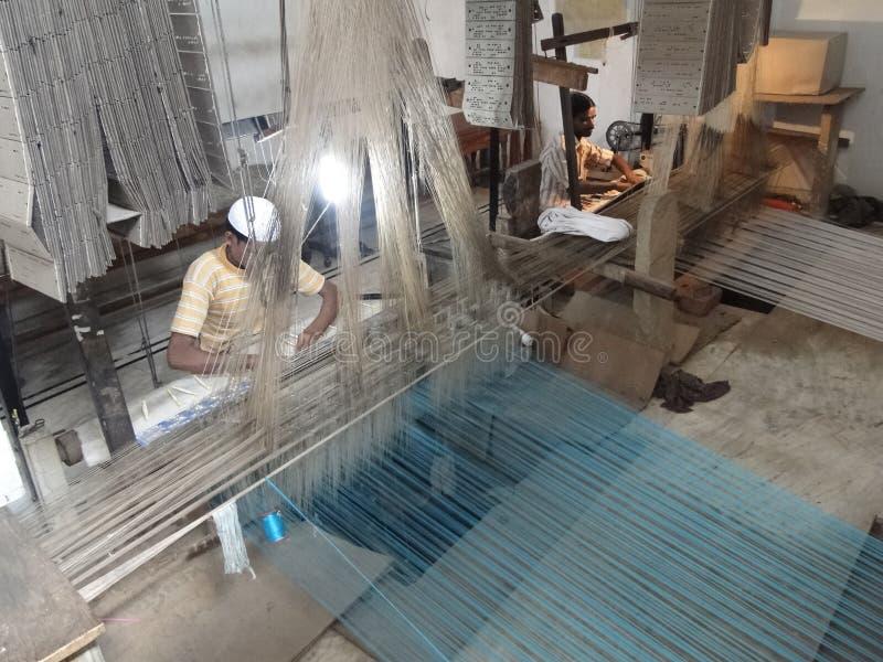 De jonge moslimmens stelt een weefgetouw in werking om zijdebrokaat te weven royalty-vrije stock afbeeldingen