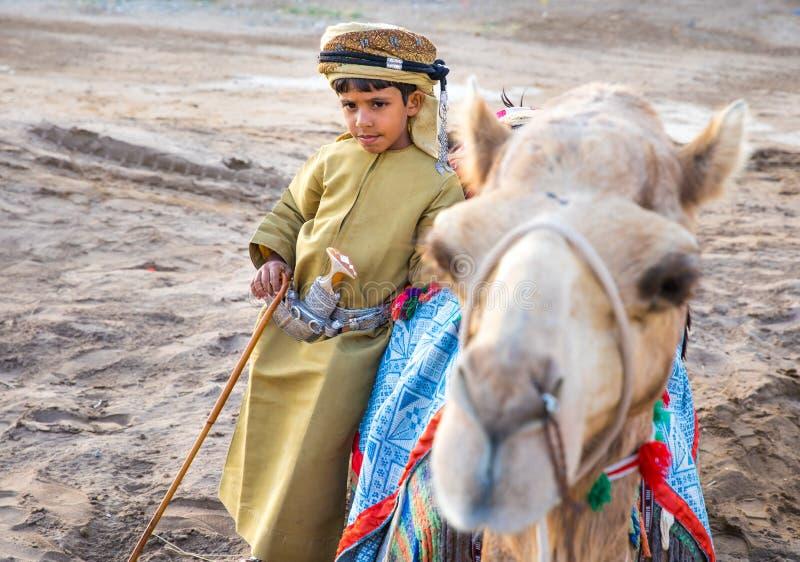 De jonge Omani jongen kleedde zich in traditionele kleding stock foto