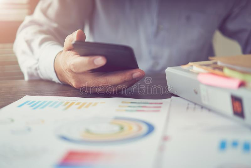 De jonge onderneemster in bureau gebruikt de telefoon aan coördinaat op de lijst stock afbeeldingen