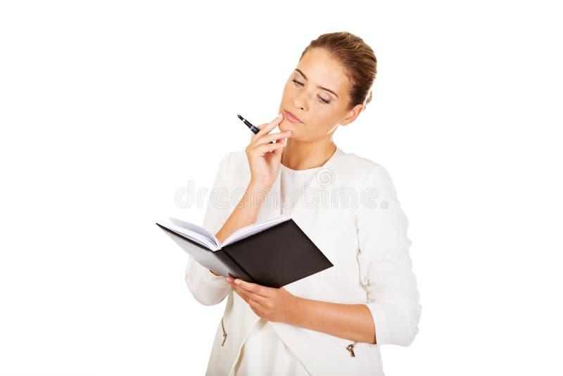 De jonge onderneemster denkt over één of ander idee en maakt nota's stock foto's