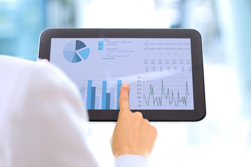 De jonge onderneemster die grafieken tonen door vinger bij de digitale tablet stock afbeeldingen