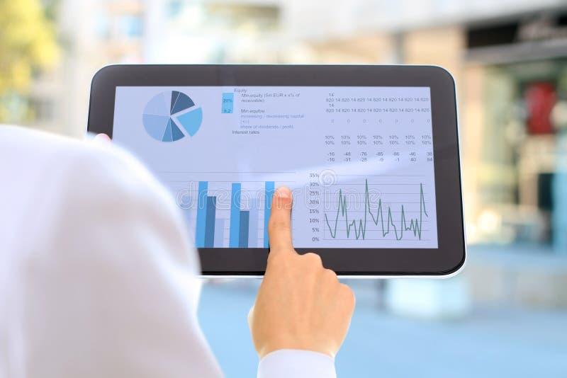 De jonge onderneemster die grafieken tonen door vinger bij digitaal stock afbeelding