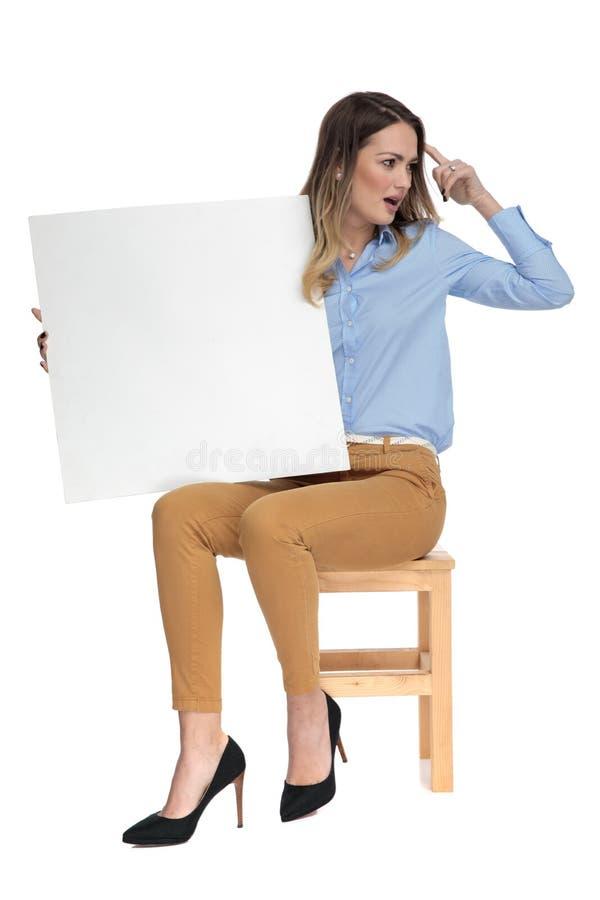 De jonge onderneemster houdt een leeg aanplakbord enkel iets herinnerde stock afbeelding