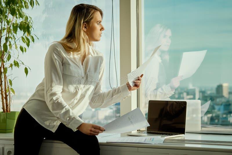 De jonge onderneemster met documenten kijkt door een venster in een wolkenkrabber royalty-vrije stock foto