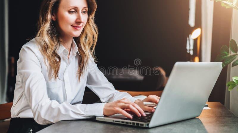 De jonge onderneemster in wit overhemd zit in bureau bij lijst voor computer, typend op laptop GLB, kaap, viering, kok, het diner stock fotografie
