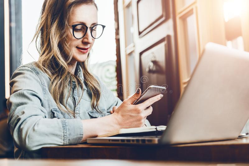 De jonge onderneemster zit in koffiewinkel bij lijst voor computer en notitieboekje, gebruikend smartphone Sociale Media royalty-vrije stock afbeelding