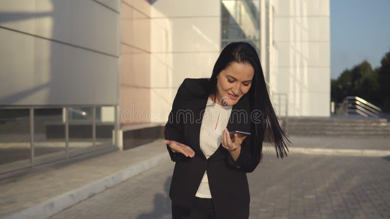 De jonge onderneemster in zwart kostuum gilt bij de telefoon op zonnige dag tegen de achtergrond van bureaucentrum stock afbeelding