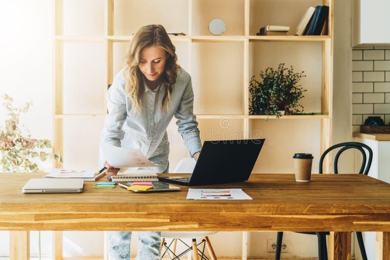 De jonge onderneemstervrouw bevindt zich dichtbij keukenlijst, lezend documenten, gebruikslaptop, het werken, het bestuderen royalty-vrije stock foto's